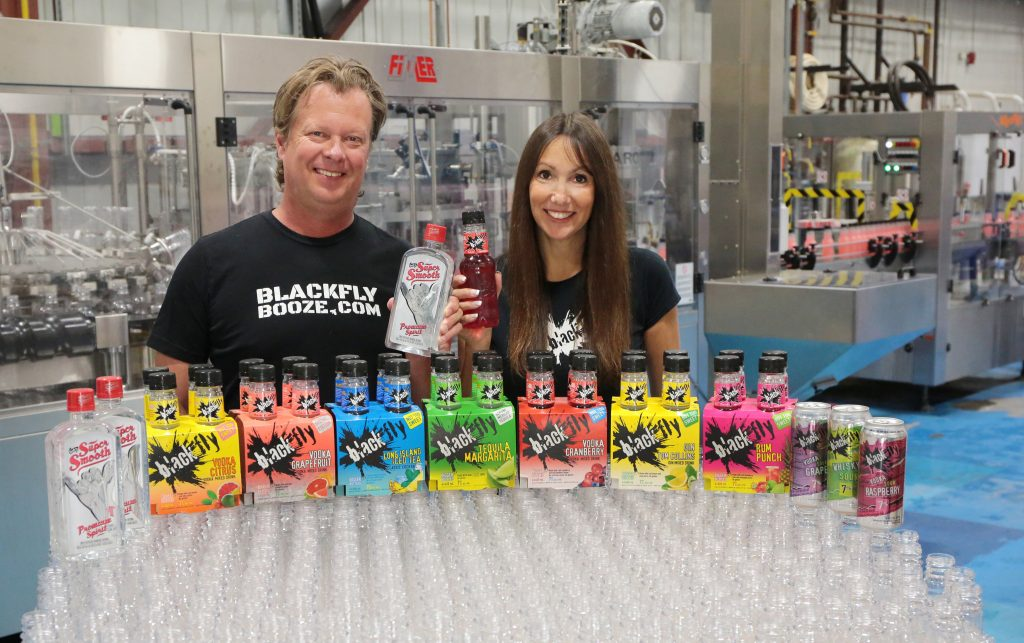 Why you should test your new products in London, Ontario. Rob Kelly and Cathy Siskind-Kelly of Black Fly Beverages each holding one of their drinks with bottles of their drinks in front of them. Photo courtesy of Cathy Siskind-Kelly.