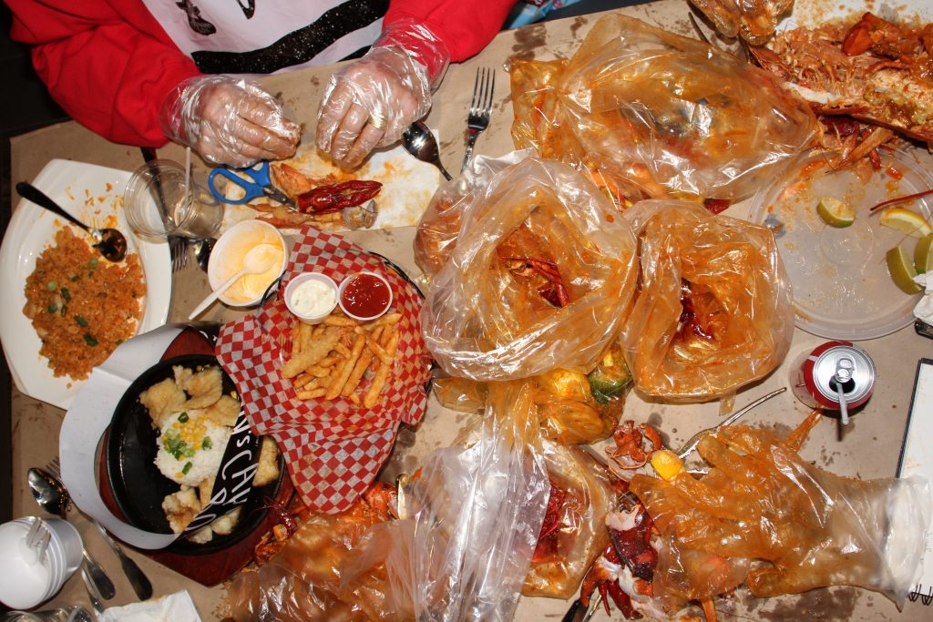 Bags of leftovers and seafood sauce are on a table