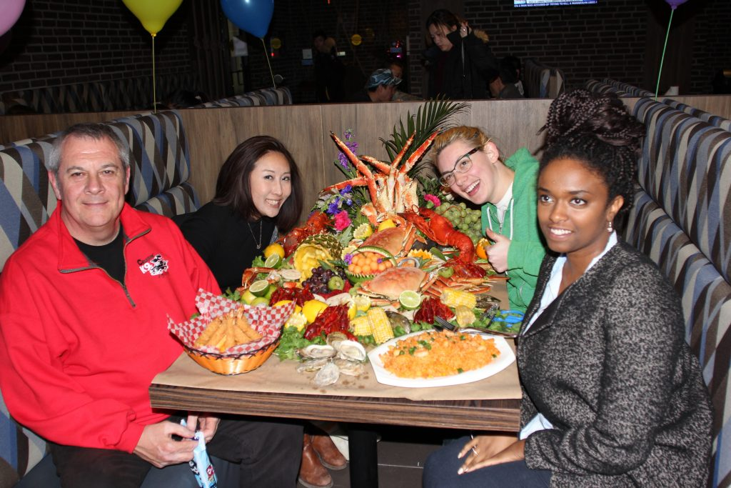 4 people are sitting at a table with a large amount of seafood in front of them