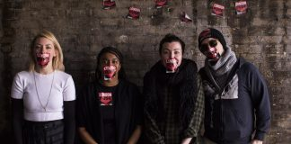 four people stand in front of a brick wall with London Fuse stickers on their mouths