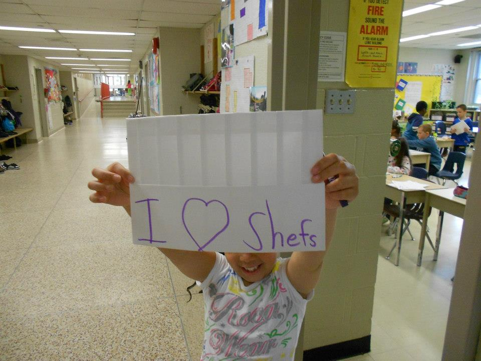 Child holding hand made sign that reads I love chefs which is misspelled