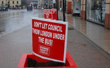 "Red signs that say ""Don't Let Council Throw London Under the Bus"" in white font. The signs are down Richmond Row in London, Ontario"