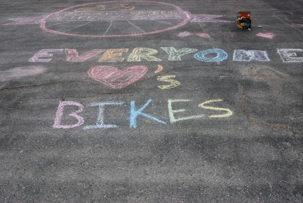 "A chalk drawing that says ""Everyone loves bikes,"" in rainbow colours. ""Loves"" is represented by a pink heart, followed by an apostrophe and an s. Photo taken at the Squeaky Wheel Bike Co-op Grand Opening"