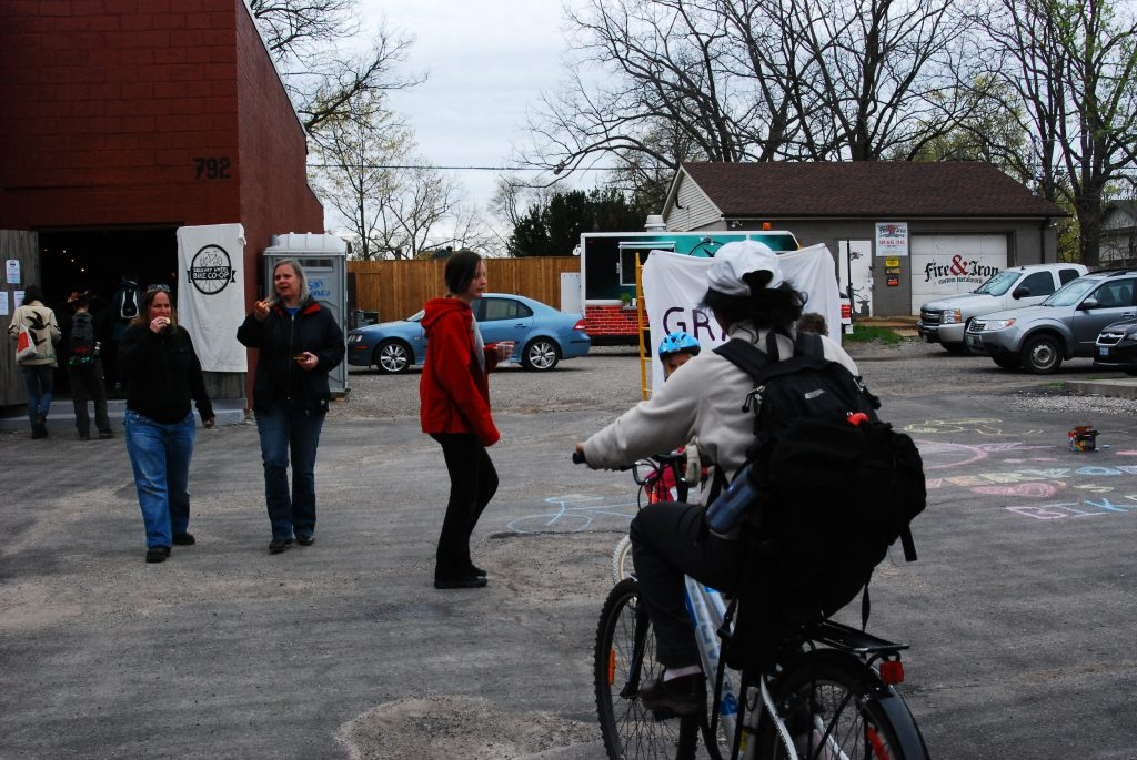 A cyclist with a white hat and a grey sweater cycling towards three people at the Squeaky Wheel Bike Co-op Grand Opening.
