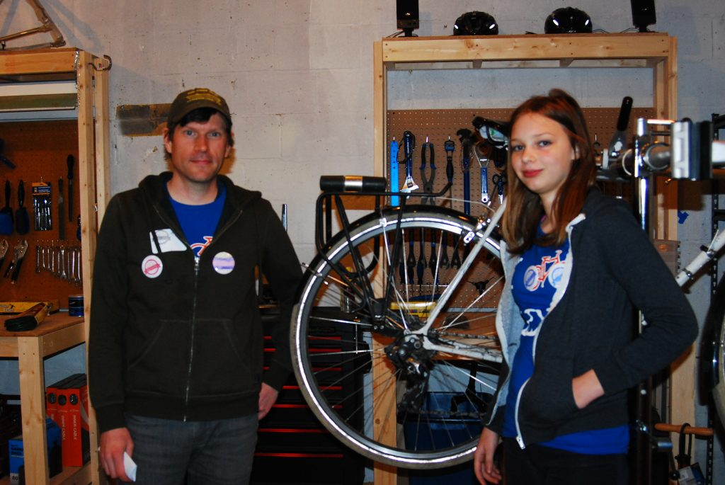 Tim Pearson (Left) and Maggie Bird standing in front of a bike wheel at the Squeaky Wheel Bike Co-op.