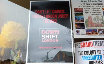 "A window with a black Down Shift London Poster that says ""Don't let council throw London under the bus!"" in red letters"