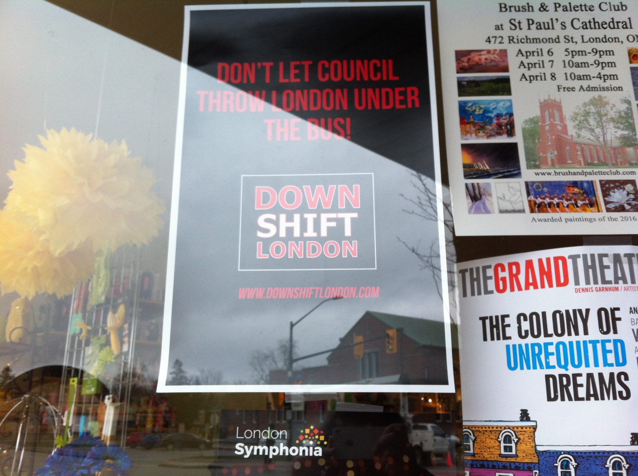 """A window with a black Down Shift London Poster that says """"Don't let council throw London under the bus!"""" in red letters"""