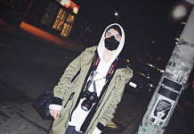 A man wears a mask over his mouth, a camera around his neck and a cargo jacket