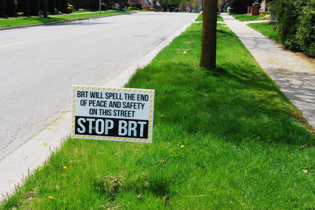 "A white sign on Doon Drive and Sunnyside Drive. It says ""BRT will spell the end of peace and safety on this street. Stop BRT."""