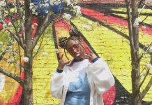 a woman stands in front of a painted brick wall making a 'hang loose' gesture with her hands