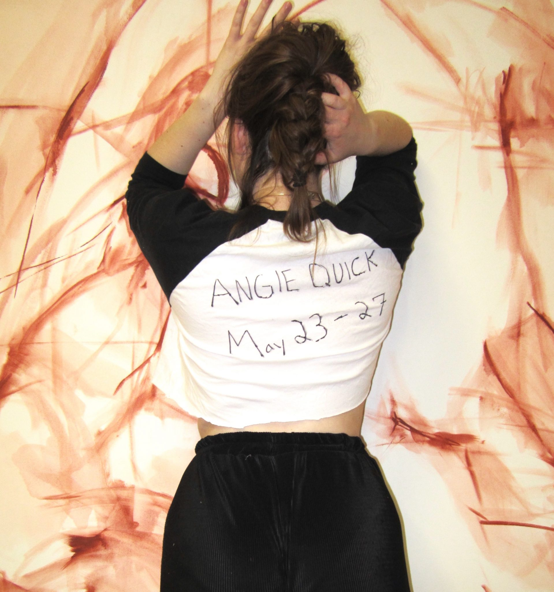 a woman stands with her back to the camera with the words 'angie quick May 23-27' on the back of her shirt