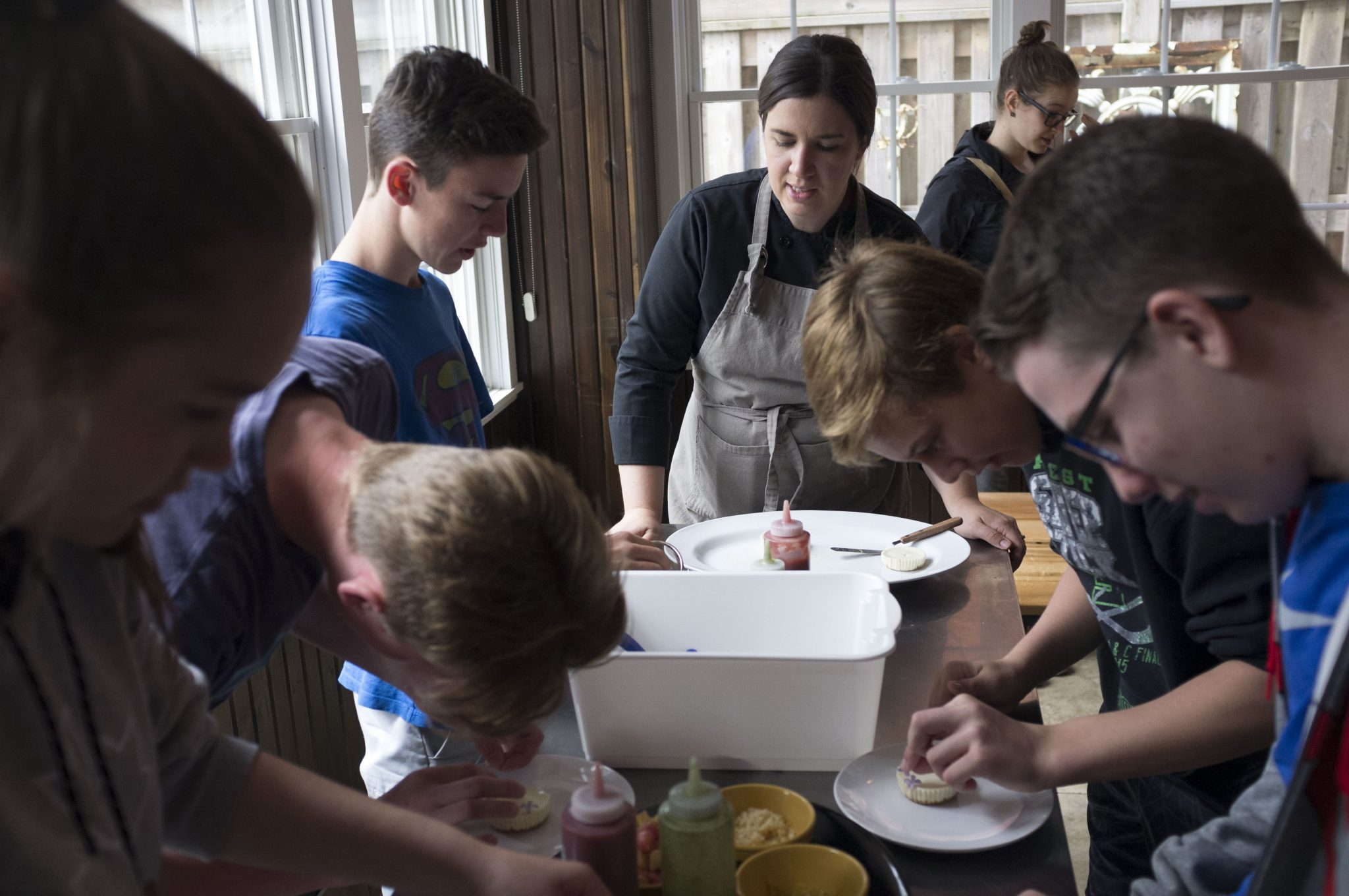 a chef works with a class of students who are making organic cheese cake cupcakes