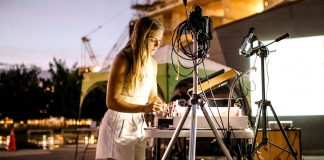 a woman is making projections using liquid paint for a live music show