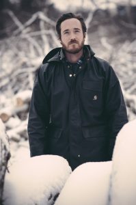 Fraser Teeple is seen standing outside in a snow covered forest setting.