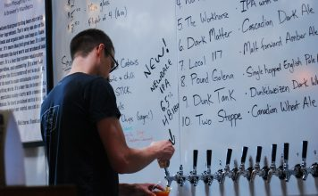A bartender at the London Brewing Co-Op pouring a beer.