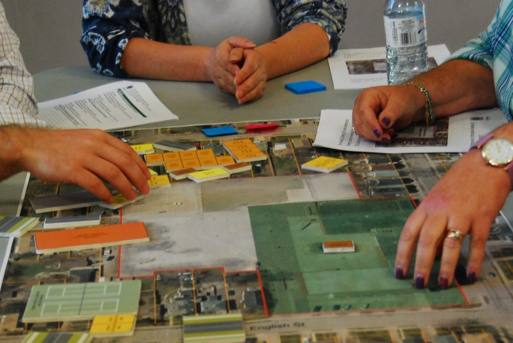 Hands on a table with sticky notes and markers to discuss the park plans for Lorne Avenue.