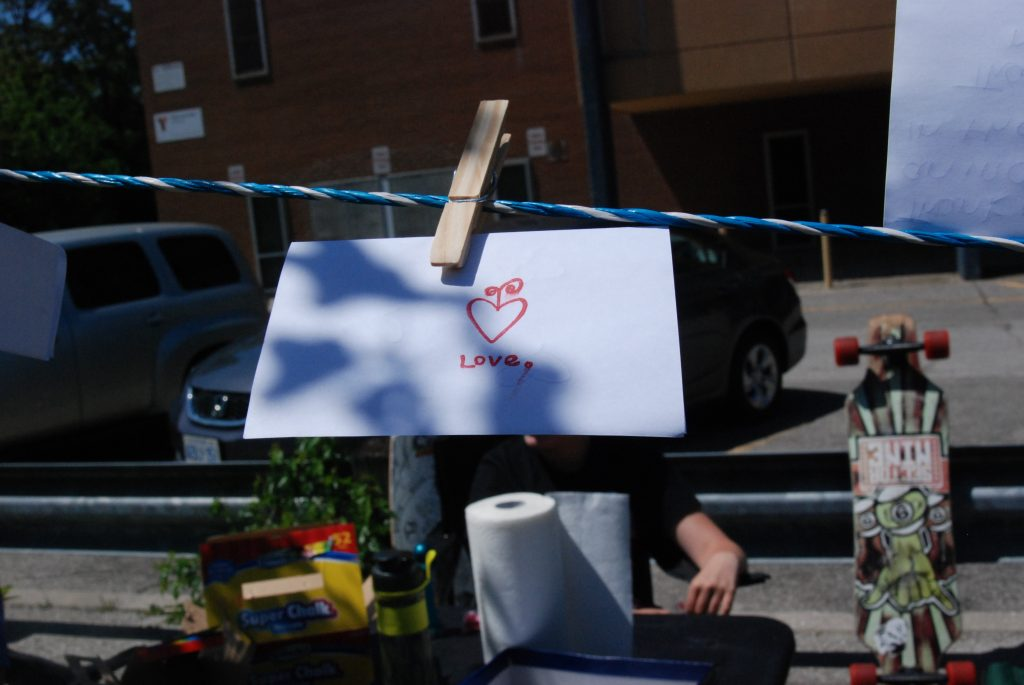 "A white piece of paper with a red heart and ""love"" in red letters on a clothes pin and clothesline."