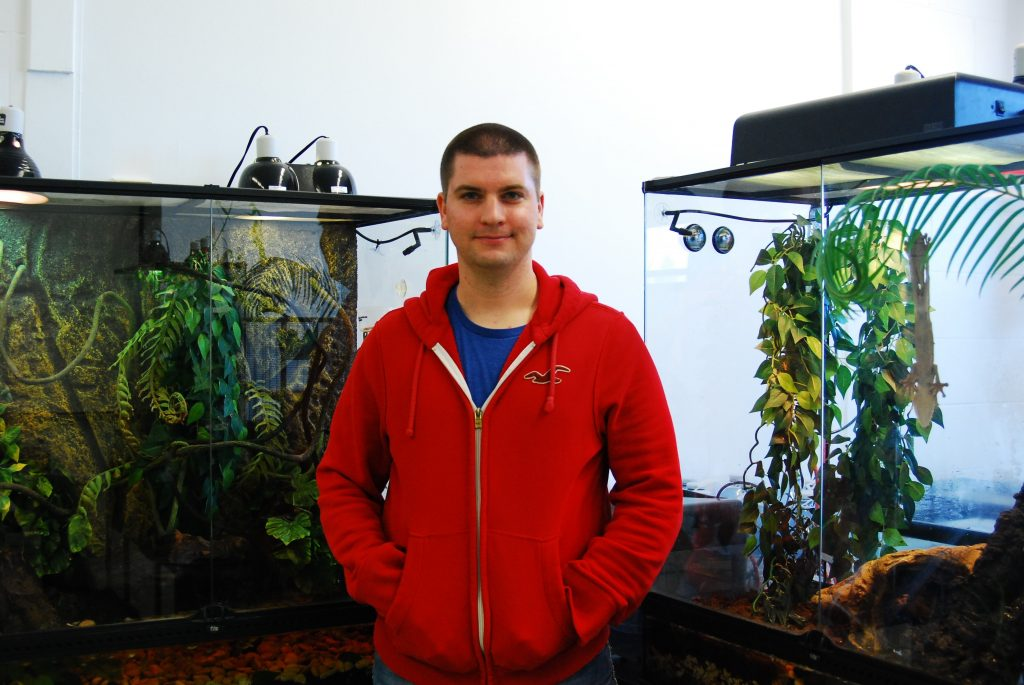 William Komer in front of two reptilian tanks at Campus Creative.
