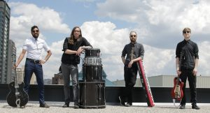 The four members of Mountain of Wolves, Richard, Brent, Will and Michael, stand on a rooftop with their instruments in this posed promo photo.