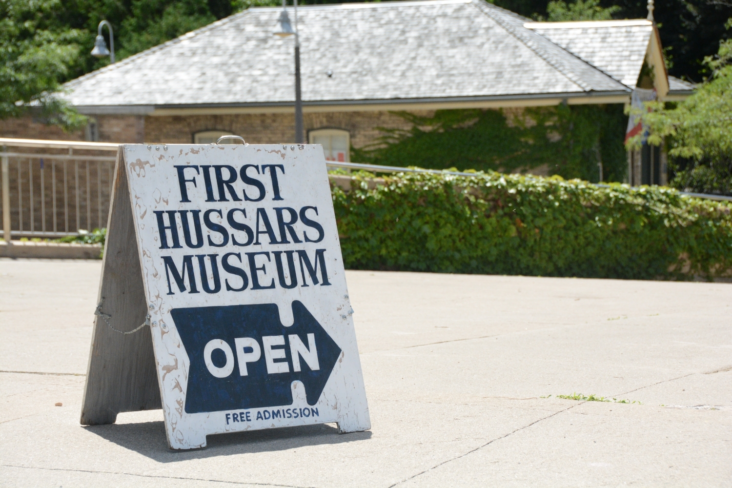 A sign for the musuem, with the short building in the background.