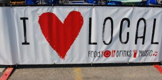"The ""I Love Local Sign"", which is white with black font and a red heart."