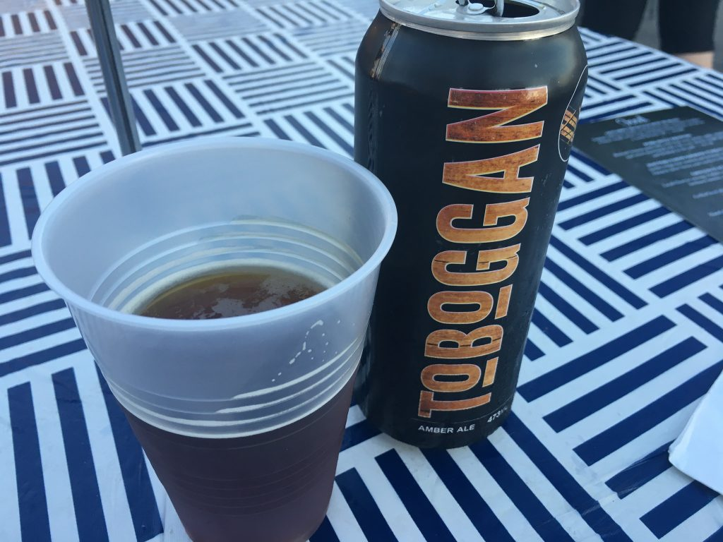 "A cup of Toboggan Amber Ale beside a black can with gold letters that say ""Toboggan"""