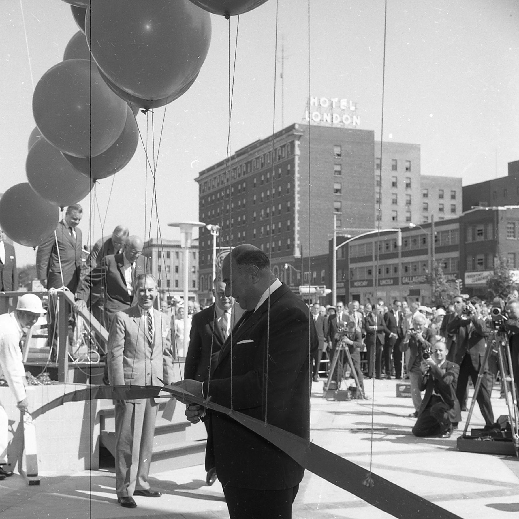 "The late Victor Aziz had his camera ready when the old Wellington Square mall had its ribbon-cutting ceremony on Aug.10, 1960 at 10:30 a.m. ""Very big deal … not sure who the ribbon cutter is. Must be a mayor or mall owner,"" says his son (working from the image, not the negative details.) So —who knows the ID of the big man channeling Edward Scissorhands. Usual prizes available via LondonFuse."