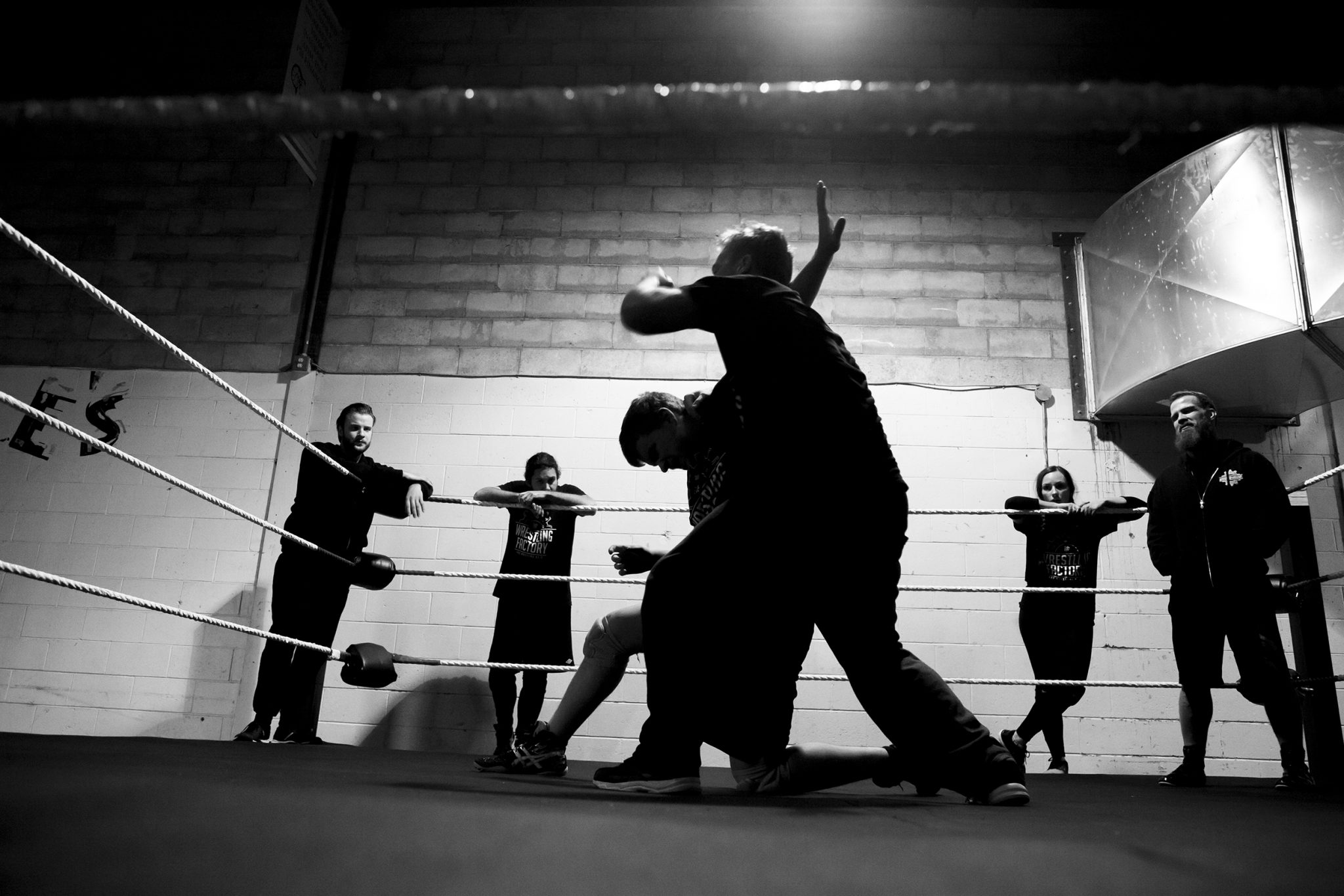 Students lock up during training. Located in the back corridors of the old Ice House, the dimly lit atmosphere suits a wrestling school perfectly.