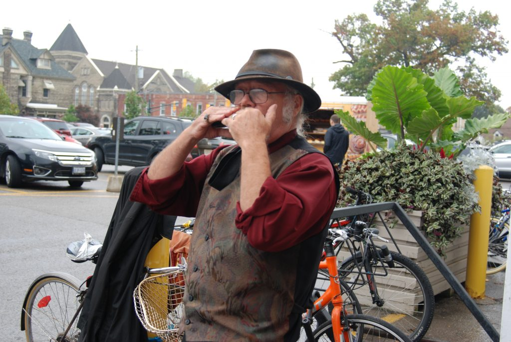 Busking at the Western Fair Farmers' Market. Terry Colfax playing the harmonica outside of The Market at the Western Fair District.