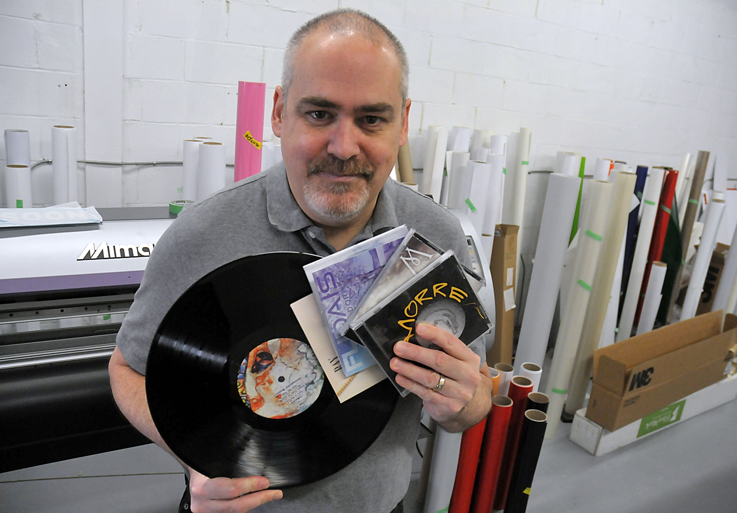 Derek Armstrong of Blu Monster Print and Media shows off just a few of the many albums he's printed over the years.