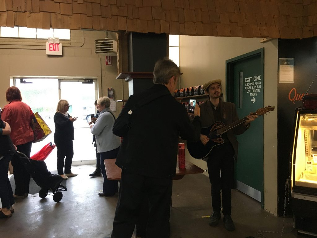 Busking at the Western Fair Farmers' Market. Steve Hillier taking videos of Lliam Buckley playing the guitar inside The Market at the Western Fair District.
