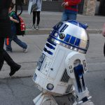 R2-D2 walking with people walking down Dundas Street in London, Ontario at Free Comic Book Day. Photo by Emily Stewart.