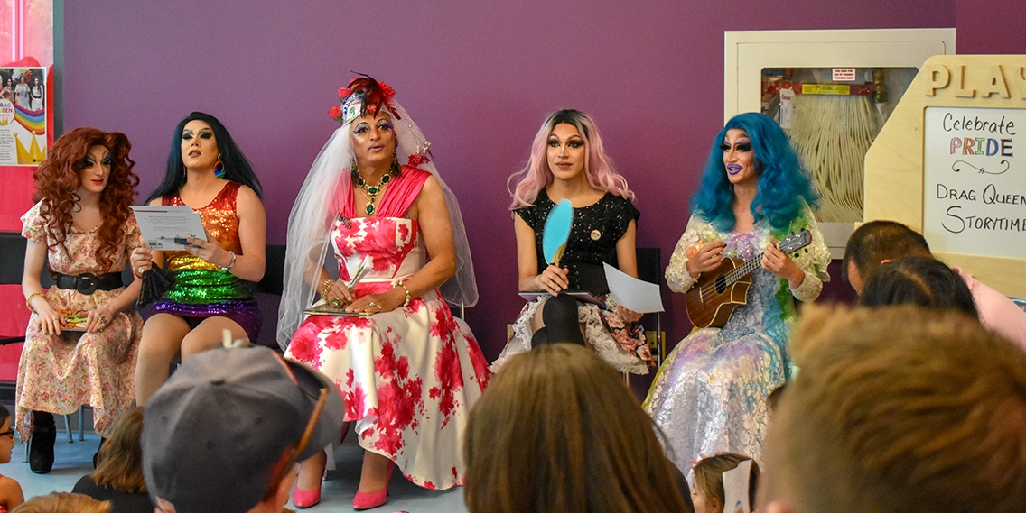 Five drag queens sit in front of a crowd; one holds a ukulele.