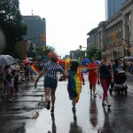 24th Annual London Pride Parade. A couple dashes through the Pride Parade in London, Ontario. Photo by Emily Stewart.