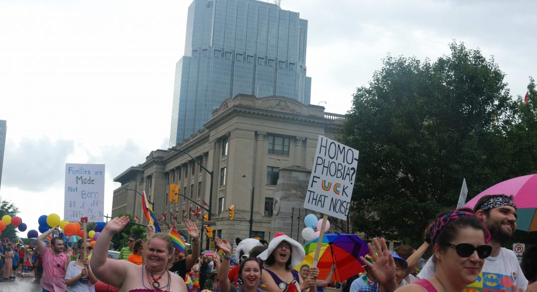 24th Annual London Pride Parade. Several people marching through the Pride Parade in London, Ontario holding signs. Photo by Emily Stewart.