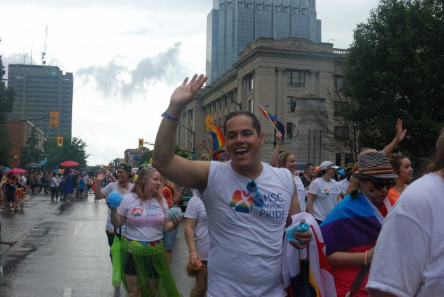 24th Annual London Pride Parade. A man waving while wearing a shirt on behalf of the London Health Sciences Centre. Photo by Emily Stewart.