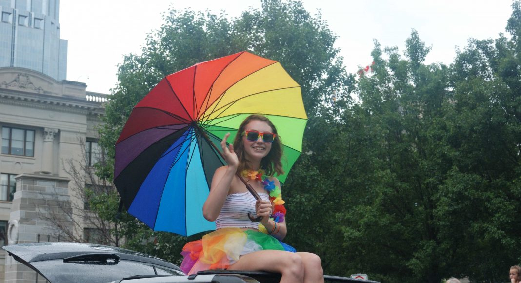 24th Annual London Pride Parade. A girl sitting on top of a car with a rainbow parasol at the Pride Parade in London, Ontario. Photo by Emily Stewart.