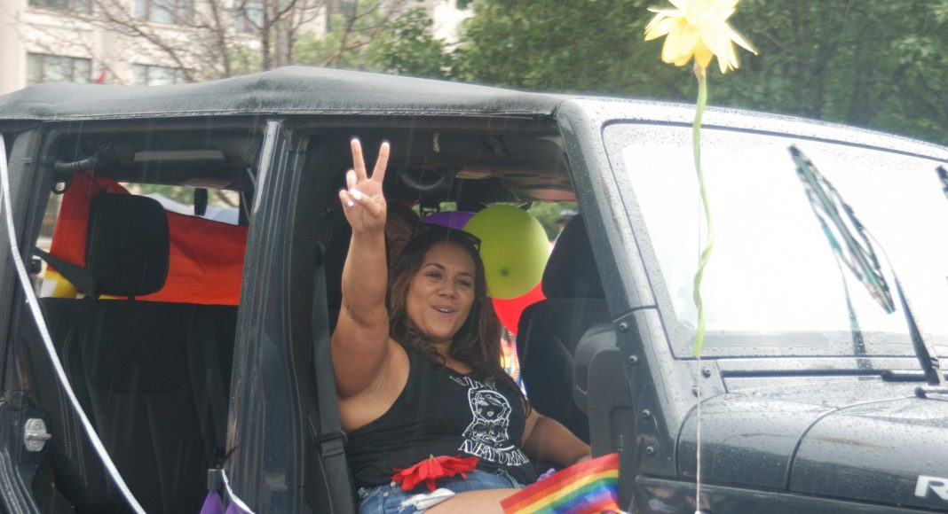 24th Annual London Pride Parade. A woman with a Purdy Natural tank top doing a peace sign from her car at the Pride Parade in London, Ontario. Photo by Emily Stewart.