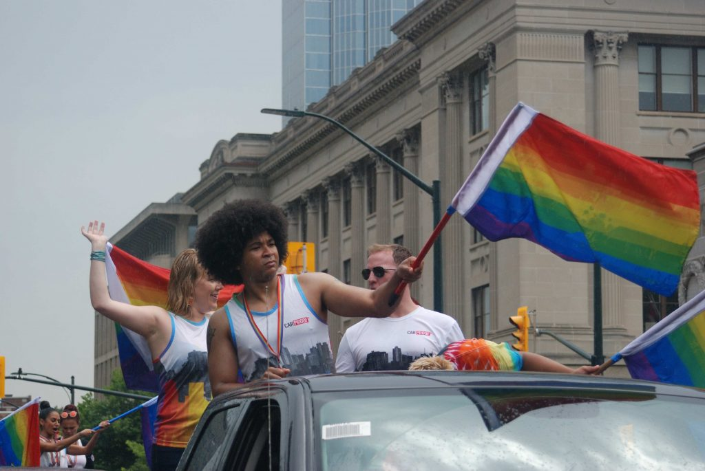 24th Annual London Pride Parade. Three people at the Pride Parade in London, Ontario. One person is waving a rainbow flag. Photo by Emily Stewart.