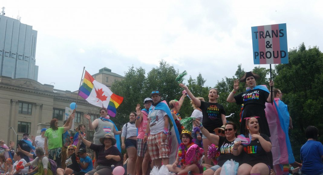 24th London Pride Parade. Several people on a Pride Parade float holding signs in London, Ontario. Photo by Emily Stewart.