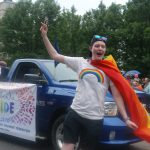 24th Annual London Pride Parade. A person dancing in the Pride Parade in London, Ontario, that is nearby a car with a sign representing the Ontario Secondary School Teachers' Federation. Photo by Emily Stewart.