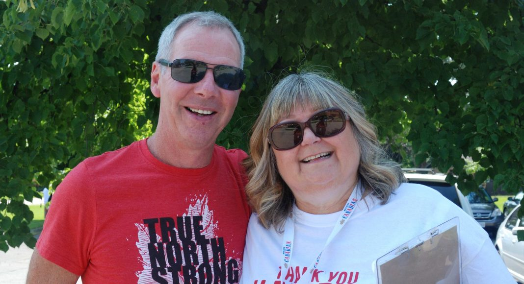 "Thank You Ilderton. A man wearing a red shirt that says ""True North Strong and Free"" and a woman wearing a white shirt that says ""Thank You Ilderton"" on it before the Thank You Ilderton Parade in Ilderton, Ontario. Photo by Emily Stewart."