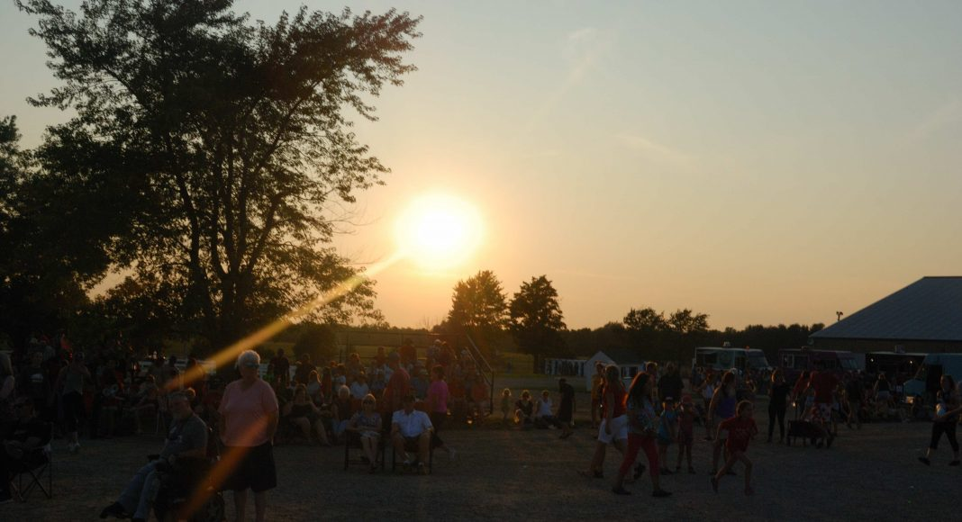 Thank You Ilderton. People at Thank You Ilderton walking around the fairgrounds and enjoying the sunset. Photo by Emily Stewart.