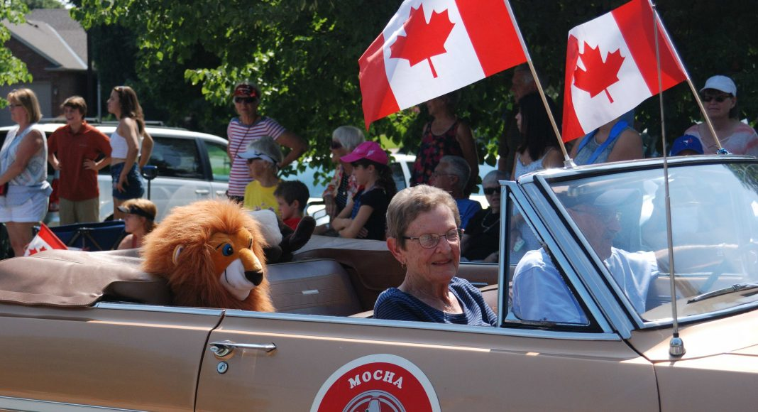 Thank You Ilderton. The Mocha Classic car, with a man, woman, and plush lion inside, driving through the Thank You Ilderton Parade in Ilderton, Ontario. Photo by Emily Stewart.