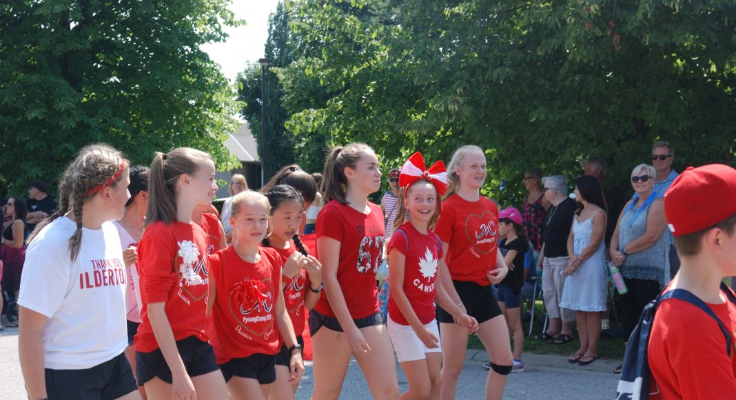 Thank You Ilderton. A group of girls in red shirts and shorts cheering in the Thank You Ilderton Parade in Ilderton, Ontario. Photo by Emily Stewart.
