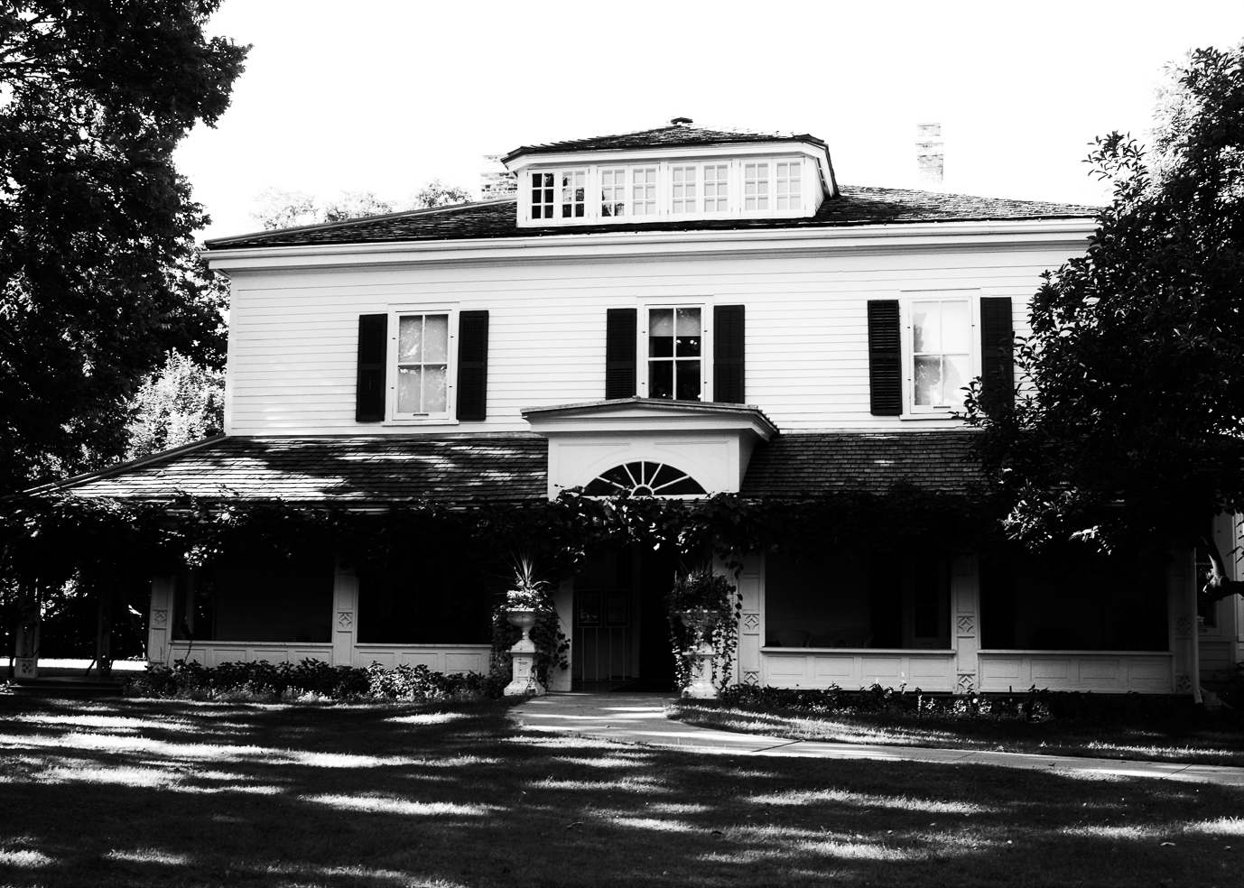 Looking for ghosts at Eldon House. A black and white photograph of the front entrance of Eldon House in London, Ontario. Photo by Emily Stewart.