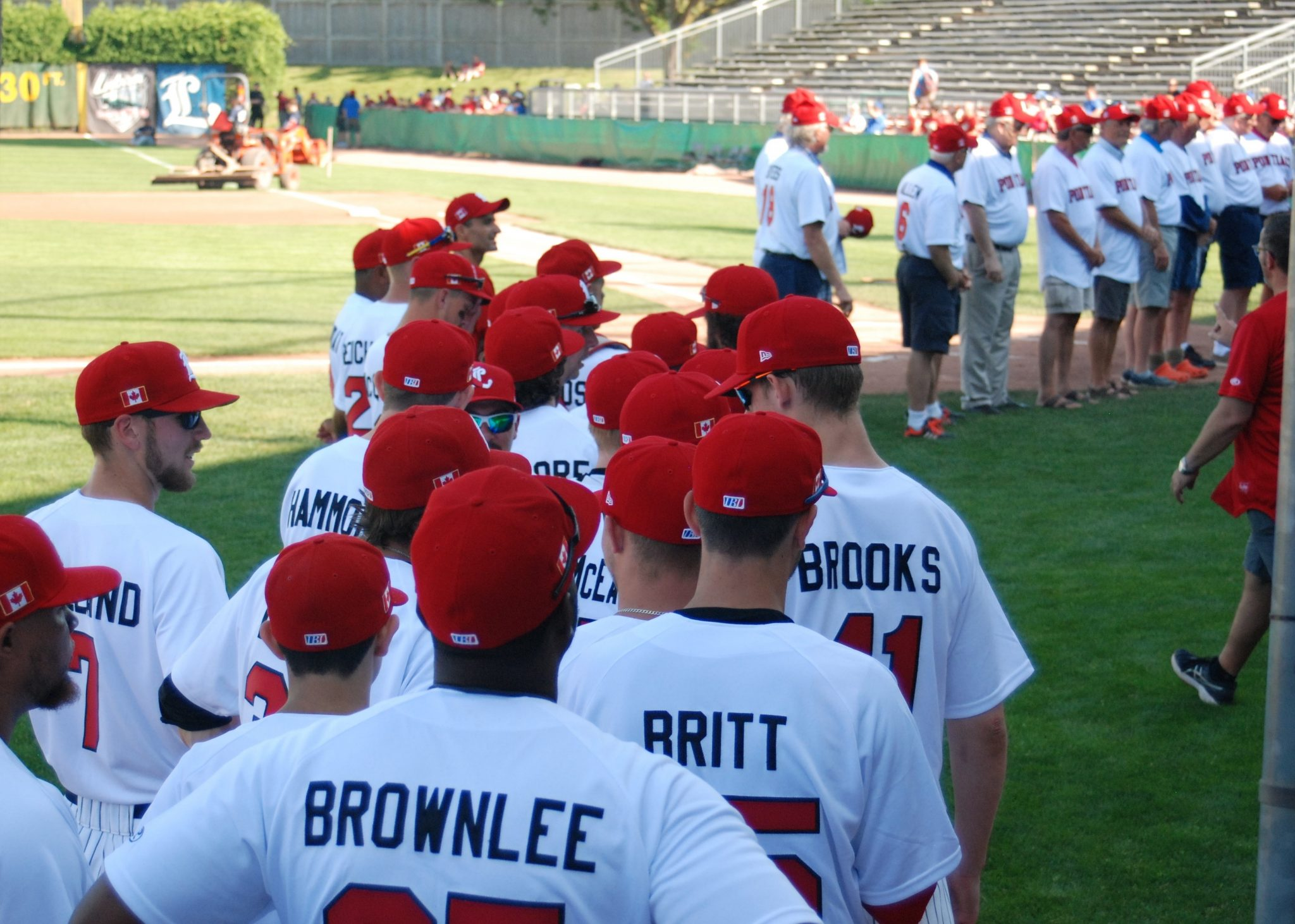 The 2018 London Majors Team in line to stand with London Majors alumni. All of them are wearing red and white London Pontiac Uniforms.