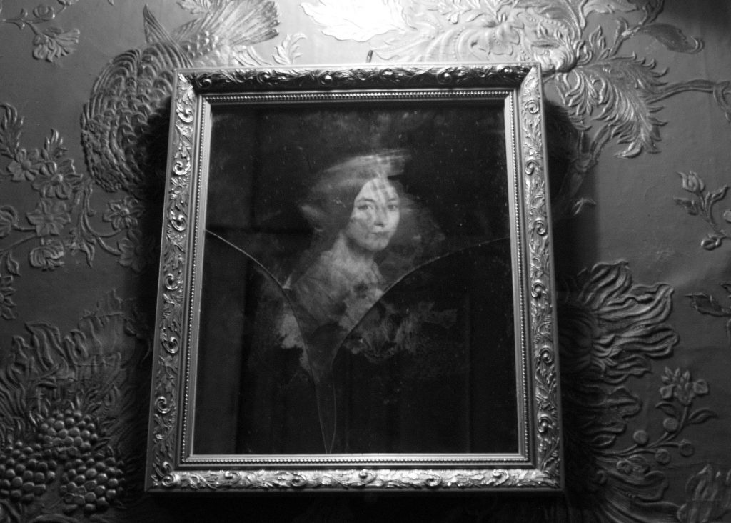 Looking for ghosts at Eldon House. A black and white photo of a woman's portrait in a broken mirror with a frame on a wallpaper covered wall at Eldon House as part of the Great Eldon House Ghost Hunt in London, Ontario.