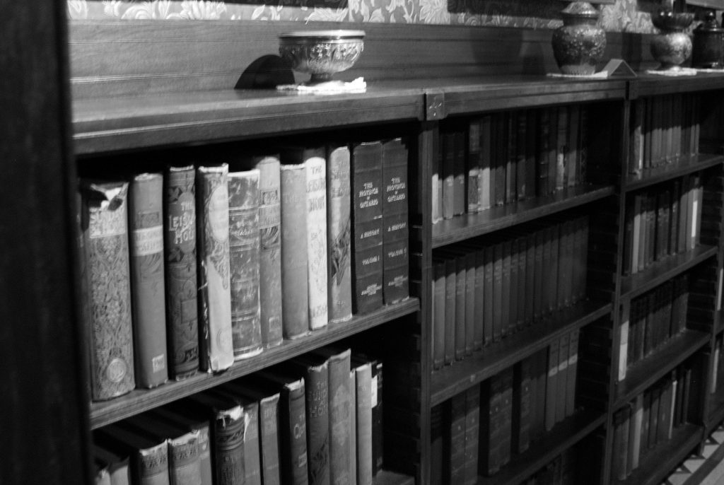 Looking for ghosts at Eldon House. A black and white photo of shelves filled with library books in the library in Eldon House. This is where the Great Eldon Ghost Hunt reveals its most famous ghost story in London, Ontario.