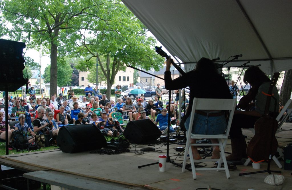 Musicians play at the Home County Music and Art Festival as the crowd watches in Victoria Park in London, Ontario.